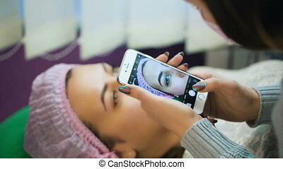 Specialist taking photo of eyebrows - Woman taking photo...