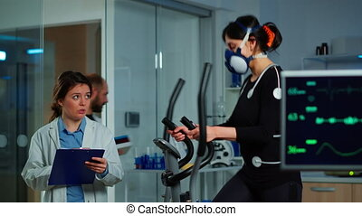 Specialists supervising exercises of patient, reading health information in clipboard, performance athlete running on cross trainer measuring heart rate, phisical endurance, psychological resistance