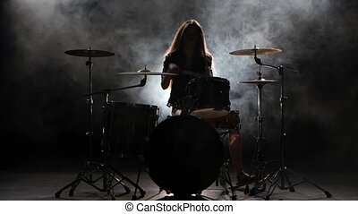 Specially trained girl plays the drums. Black smoke background. Silhouette
