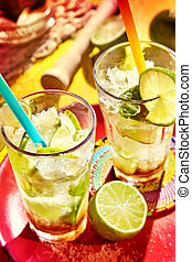 Two tall clear drinking glasses filled with ice cold Brazilian specialty of caipirinhas and topped with limes and straws