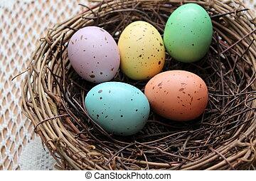Colorful speckled easter eggs in cozy twig nest.
