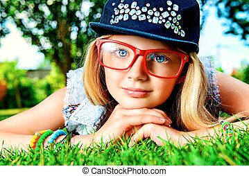 spectacles - Modern girl teenager lying on a grass in the ...