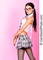 spectacles - Sexy student girl posing over pink background.