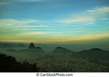 Spectacular aerial view over Rio de Janeiro as viewed from Corcovado. The famous Sugar Loaf peak sticks out of Guanabara Bay