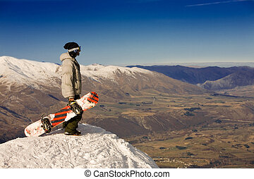Spectacular alpine view - A snowboarder stands on a peak...