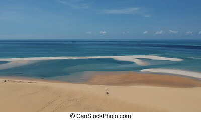 Spectacular bird's eye view sea and beach panorama with two distant people on sand. Drone shot.
