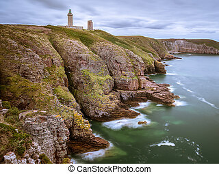 Spectacular cliffs in Cap Frehel with lighthouse on a cloudy day in summer