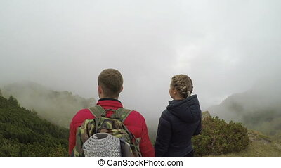 Spectacular high view of mountain landscape full of floating mist admired by young couple of tourists holding hands and kissing tourism concept