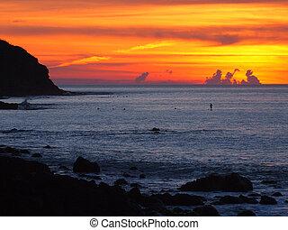 spectacular sunset over rocky surfbeach