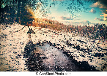 Spectacular sunset over snow covered country road