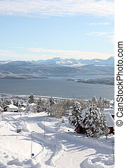 Spectacular view over a winter neighborhood, fjord, and mountains in western Norway