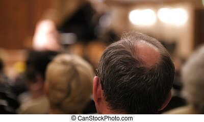 Spectators are watching theatrical performance - bald man,...