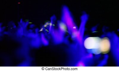 Spectators at rave party, view from behind, hand and heads...