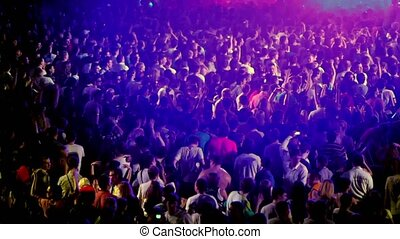 Spectators at rave party with color light flashes
