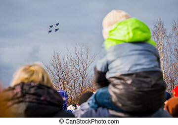 Spectators from behind watch russian fighter jets flying in clear blue skies. Fighter flies over city against dark cloudy sky. Column military warplanes flies over ground in honor of victory parade