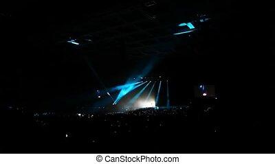 spectators sit in big concert hall and look running light beams of beginning show
