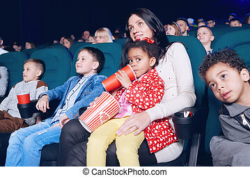 Spectators sitting in movie theatre and enjoying film, eating snacks.