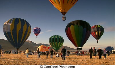 spectators watch as hot air balloons ascend into the sky