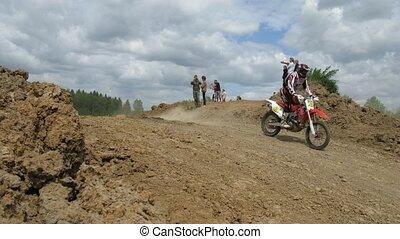 Spectators watch racers jump during enduro race
