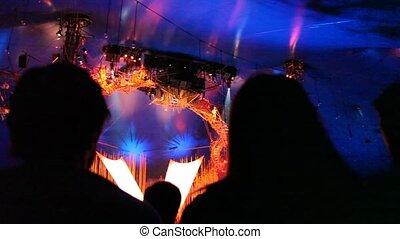 spectators watching show of acrobats in circus