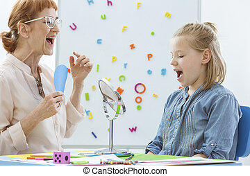 School counselor during speech and language rehabilitation with small girl