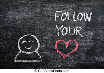 """Speech bubble with a cartoon figure and the phrase """"Follow your heart"""" drawn on a blackboard background"""