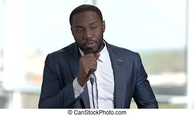 Speech of african speaker in suit.