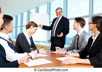 Smart and confident boss pointing at whiteboard and looking at managers during presentation