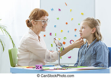 Speech therapist exercising with child in preventing speech...