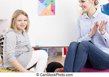 Speech therapist smiling at little girl