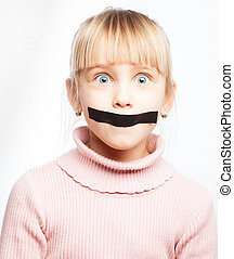 Portrait of little girl with duct tape on her mouth - silenced child concept