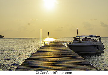 Speed boats moored at the wooden bridge in the sea and Golden reflections of the Sun