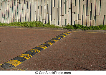 Speed bump. - A black and yellow speed bump, rumble strip...