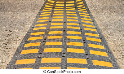 Speed bump on a road. - Speed bump on a road when a car is...
