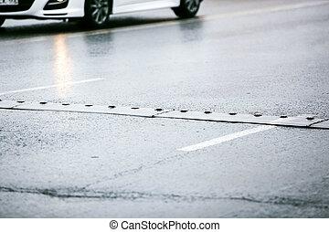 speed bump on wet asphalt road
