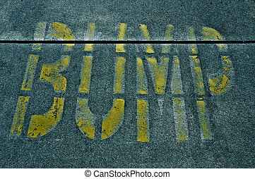 speed bump sign painted on the road