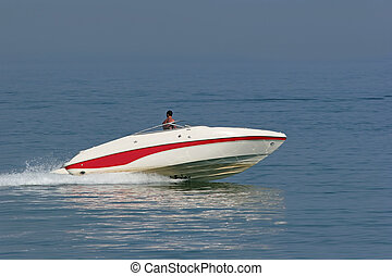 Man in a powerful white and red speed boat on the sea.