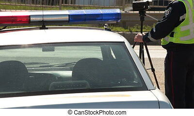Speed Limit Enforcement - Police officer holding radar speed...