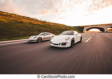 Speed motion between two sport cars across mountains