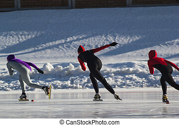 Speed skating competition on ice rink at winter sunny day - children's sport concept