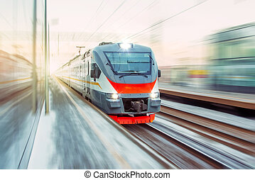 Speed suburban train with motion blur rides city station.