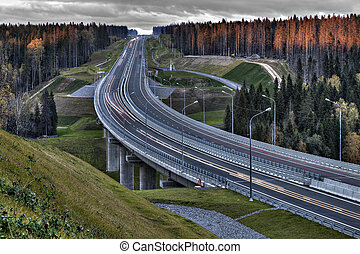 Speed track in Russia at sunset, crosses the autumn forest....