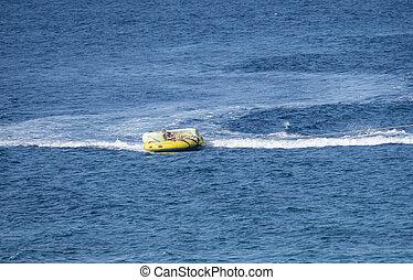 speedboat people tubing on the blue sea