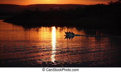 Speedboat under the sunset - A scenic shot of a lake during...