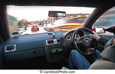 Speeding - A man speeding in a car in a built up area.