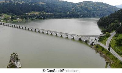 Speeding car on bridge. Bicaz mountain river bridge and...