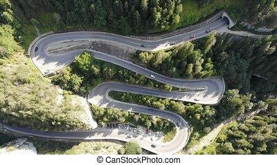 Speeding car on curvy forest road. Road traffic in Bicazului...