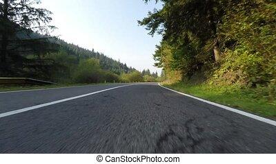 Speeding down side camera on a beautiful road through...