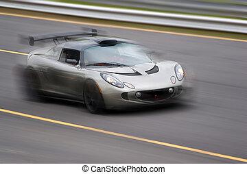 Speeding Sports Car - A fast silver sports car speeding down...
