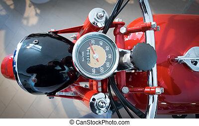 speedometer of a vintage red motorcycle